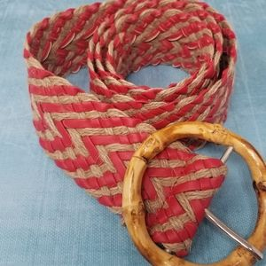 Red tan belt with round wooden buckle.